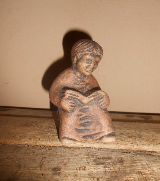 figurina din lut cu baiat citind